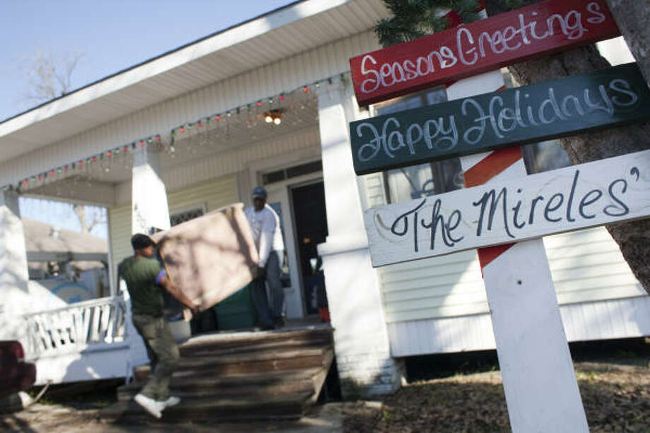 Movers Samuel Kemper, left, and Ray Osborne pack and remove furnishings Friday at the home of Eloise Mireles and her husband, Daniel, in the 4500 block of Brady. The items inside may have been bought with stolen funds, prosecutors say. Photo: Eric Kayne, Chronicle