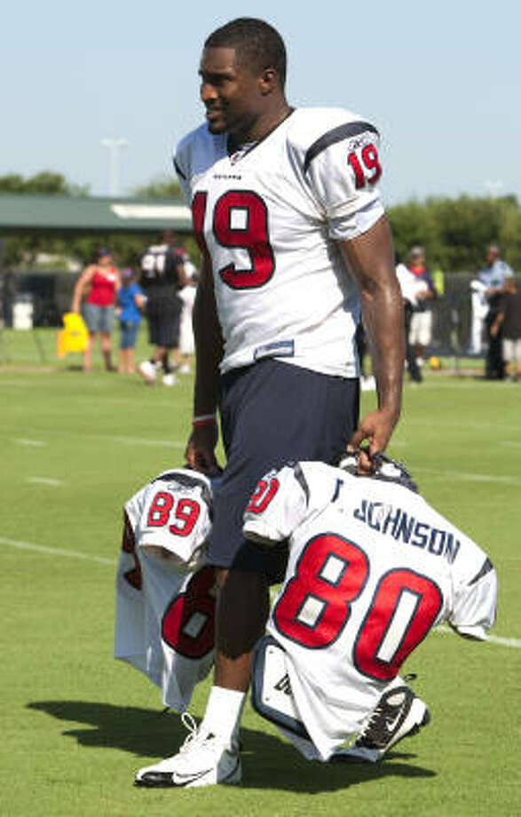 As is tradition for most NFL rookies in training camp, Texans receiver Dorin Dickerson (19) carries the pads of veterans David Anderson and Andre Johnson. Photo: Brett Coomer, Chronicle