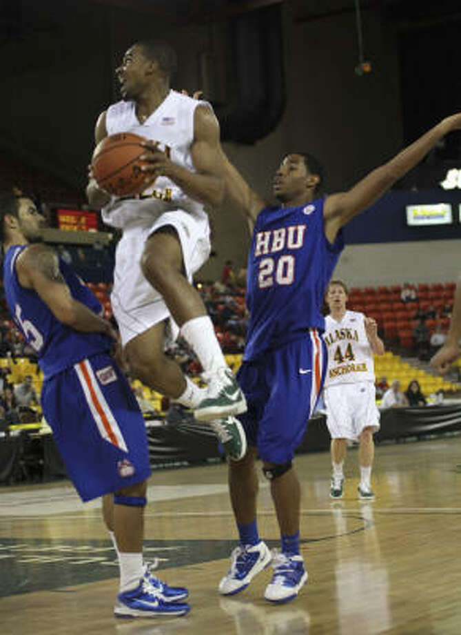 Alaska-Anchorage's Brandon Walker, top, jumps up for a shot past Houston Baptist players Jonathan Evans and T.J. Berry (20) on Friday. Photo: Rob Stapleton, AP