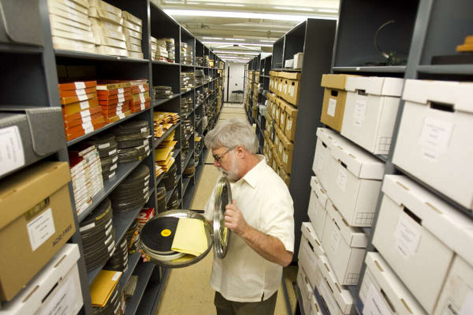 Jim Fisher, special projects producer at KUHT, examines a canIster of film containing one of the station's  shows from the 1960s in the M.D. Anderson Memorial Library's archival vault. Photo: Nick De La Torre, Houston Chronicle