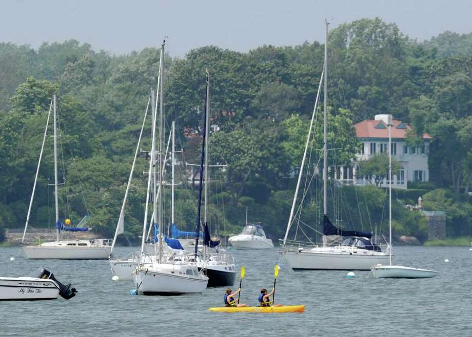 A pair of kayakers make their way through moored boats in Greenwich Cove Thursday afternoon, July 21, 2011. Photo: Bob Luckey / Greenwich Time