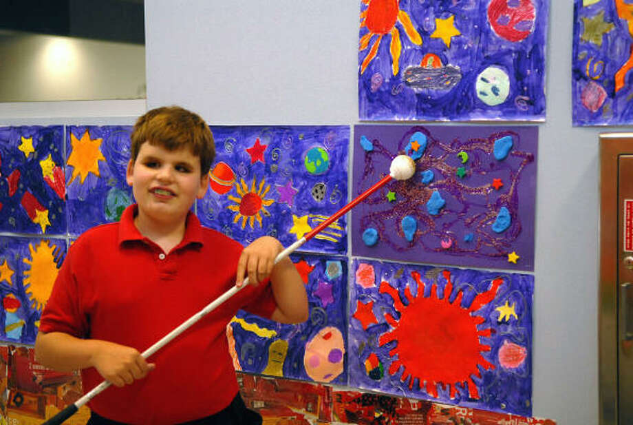 "Frost Elementary third grader Will Walsh,9, points out his artwork titled ""Space Exporation."" Photo: Ernie Chan, For The Chronicle"