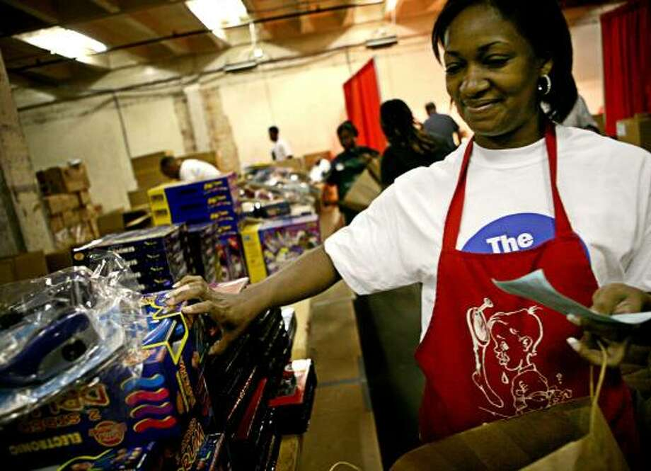 Goodfellows worker Kathy Williams distributes Christmas toys to needy families in December. Last year, donors contributed more than $1 million for Goodfellows gifts, a record for the charitable holiday program that the Houston Chronicle began on Thanksgiving 1912. Photo: ERIN TRIEB, FOR THE CHRONICLE