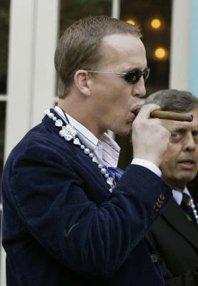 Indianapolis Colts quarterback and Super Bowl XLI MVP Peyton Manning enjoys a cigar on Bourbon Street during Mardi Gras in New Orleans. Photo: Alex Brandon, AP