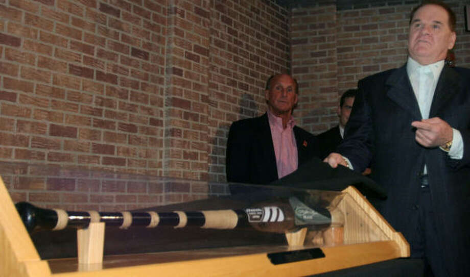 Pete Rose, right, shows the bat and baseball he used to get hit number 4,192 at the opening of a special exhibit at the Cincinnati Reds Hall of Fame. Photo: Tom Uhlman, AP