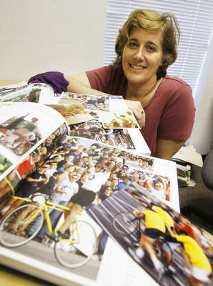 Unofficial Beer Bike historian Jen Cooper shows a Rice newspaper and yearbook featuring the tradition. This year is the 50th anniversary for the event. Photo: Kevin Fujii, Chronicle