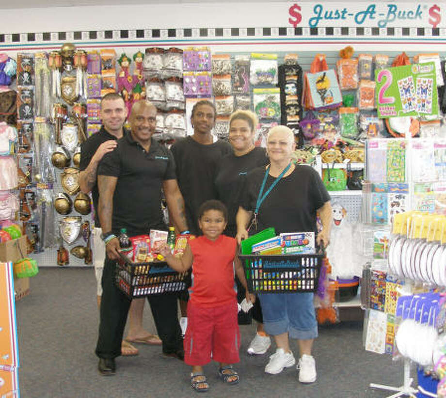 Displaying some of the merchandise at the new Just-A-Buck store in Humble are from the left at back, Chris Bryon, store opening coordinator for Just-A-Buck, and Daniel Jimenez. In the middle are storeowners, Orlando and Angelina Jimenez. Standing in front are Chansirel Jimenez and co-owner Nelly Gomez Photo: Harry Williamson