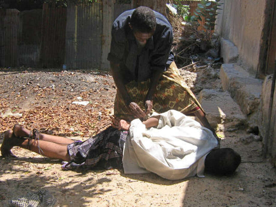 A man accused of being a spy is tied up Tuesday by an insurgent at a base in Mogadishu, Somalia. Photo: ABDI FARAH, AP