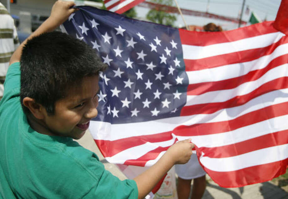 Nine year-old Anthony Aviles waves the U.S. flag before an immigration march in Houston. Photo: Billy Smith II, CHRONICLE