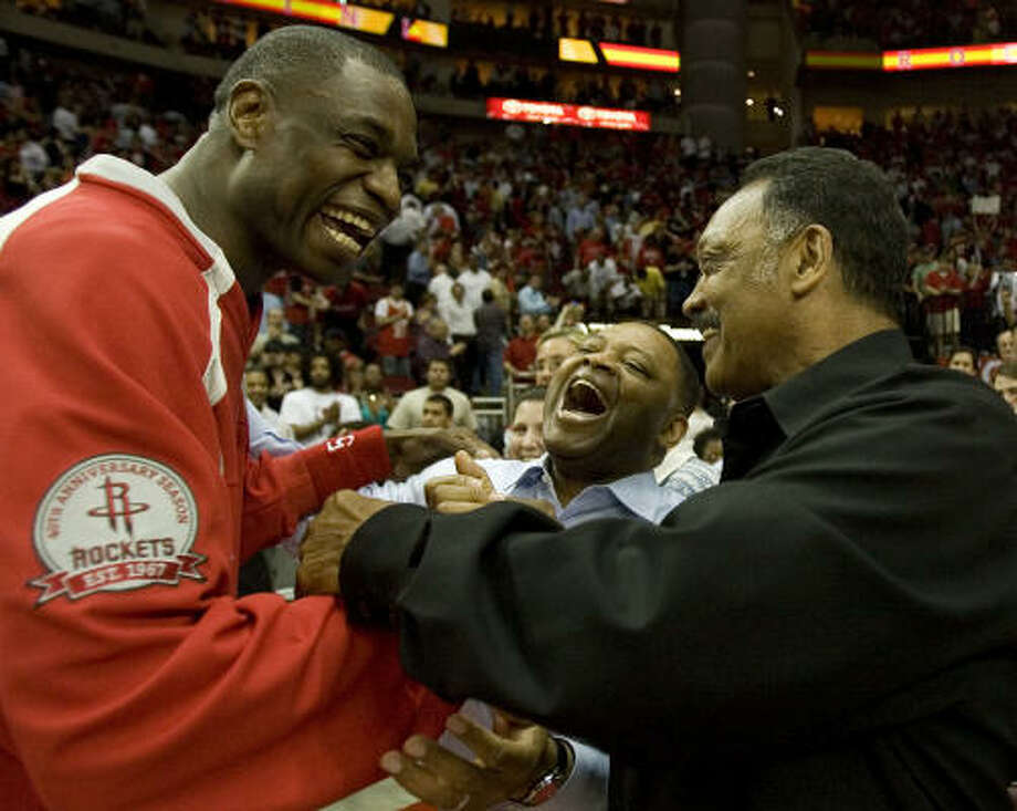 Center Dikembe Mutombo celebrates Monday's win with Rev. Jesse Jackson and Kase Lawal. Photo: Smiley N. Pool, Chronicle