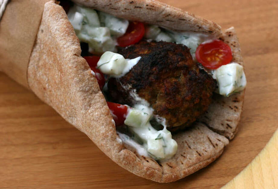 Kofta, a meatball often found in the Middle East and India, is wrapped in pita bread and served with yogurt sauce and tomatoes. Photo: LARRY CROWE, Associated Press