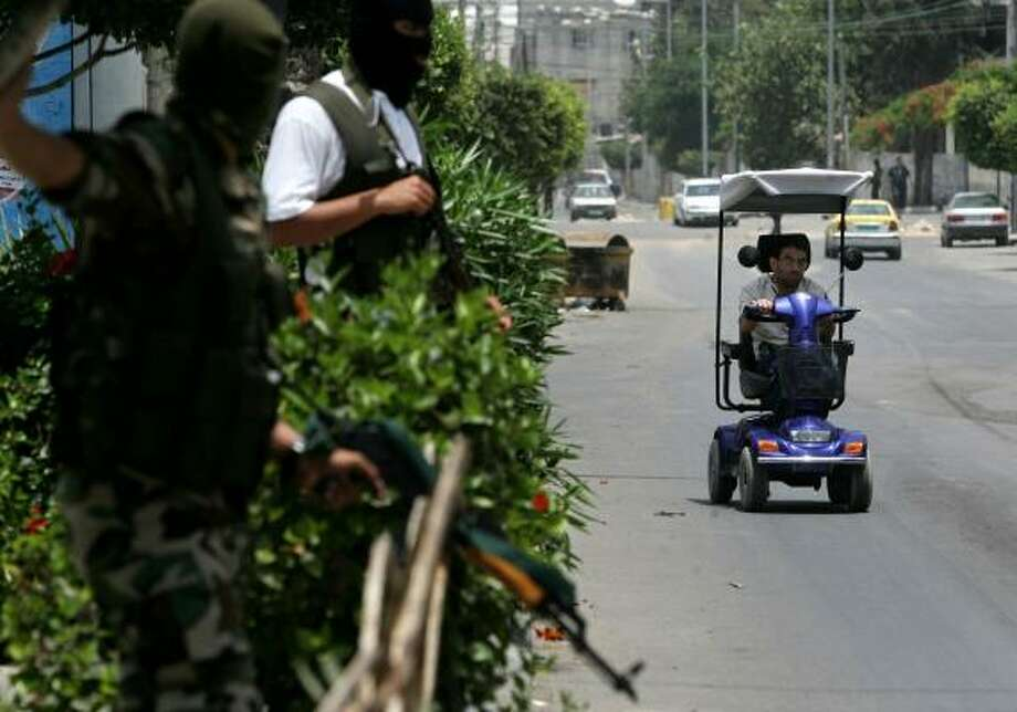 A disabled man rides past two masked Fatah gunmen Monday in Gaza City. Fighting between Fatah and gunmen loyal to Hamas, disrupted a temporary truce that had been called to allow high school students to take their final exams. Photo: ABID KATIB, GETTY IMAGES