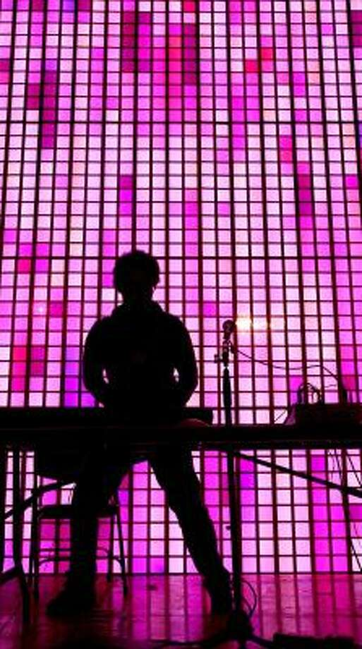 A performance artist is silhouetted by bright stage lights at the Blip Festival. Photo: CRAIG RUTTLE, ASSOCIATED PRESS