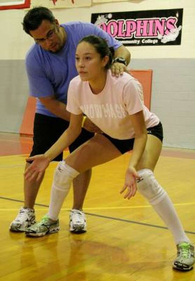 Alvine Community College volleyball coach Geoff Kiessling works with Deer Park graduate and ACC sophomore Trini Reyes in preparation for the season. Photo: Alvin Community College