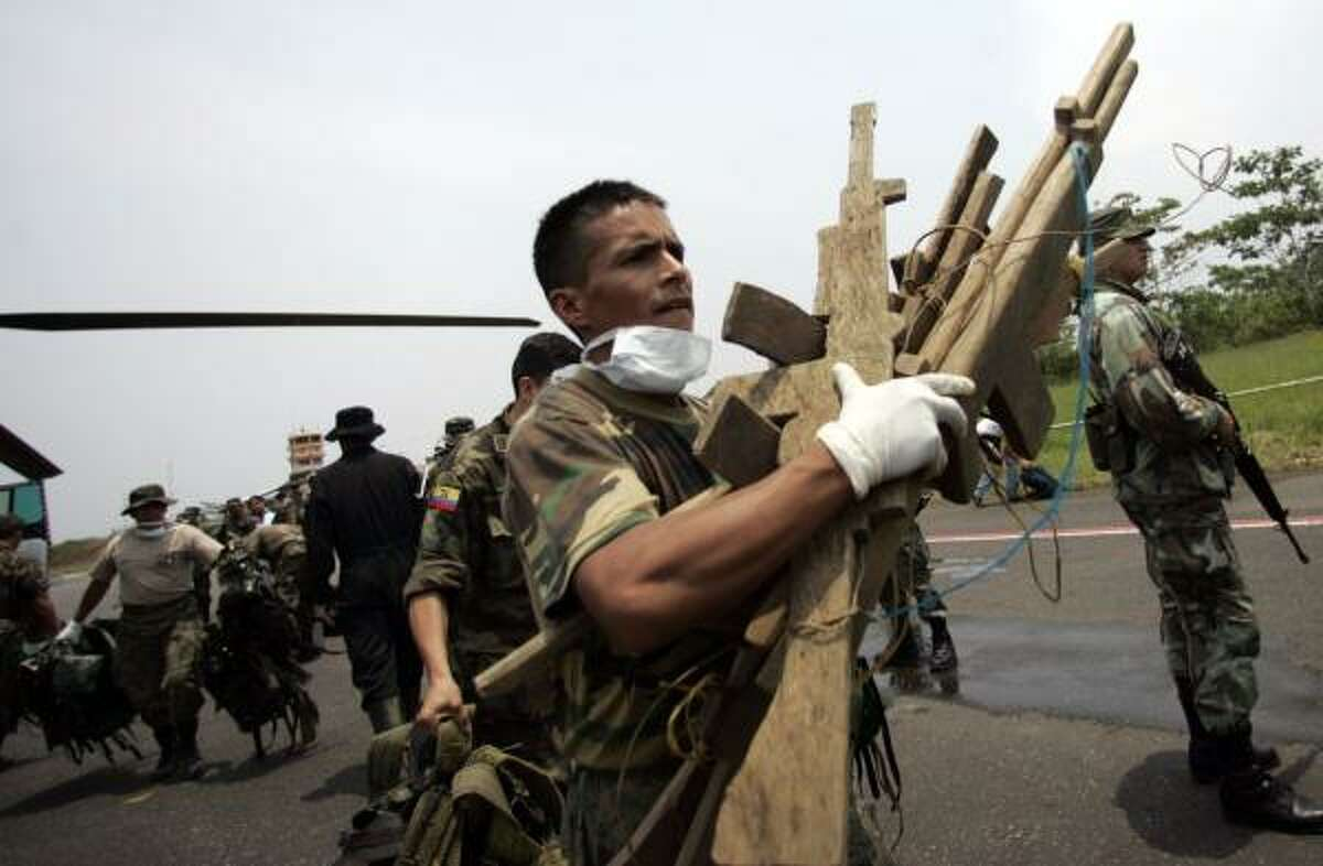 While investigating a rebel camp near the Colombian border, Ecuadorean soldiers collect wooden rifles Tuesday that the members of Revolutionary Armed Forces of Colombia used for military training.