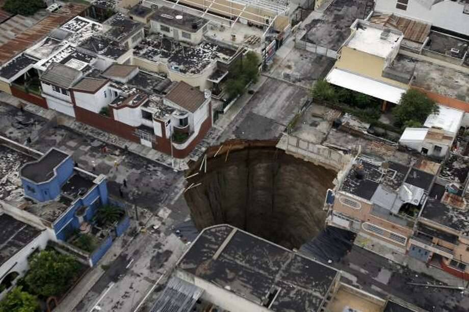 A sinkhole covers a street intersection in downtown Guatemala City,  Wednesday, June 2, 2010.  Authorities blamed heavy rains caused by  tropical storm Agatha as the cause of the crater that swallowed a a  three-story building but now say they will be conducting further studies  to determine the cause. Photo: The Associated Press
