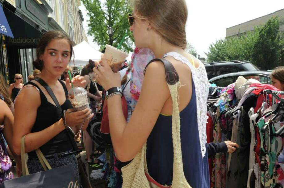 Emily Duarte, 14, and Charlotte O'Connell,14, both from Rye, N.Y., carry cold drinks to cool themselves while they shop the Greenwich Sidewalk Sale Days on Thursday, July 21, 2011. Photo: Helen Neafsey / Greenwich Time