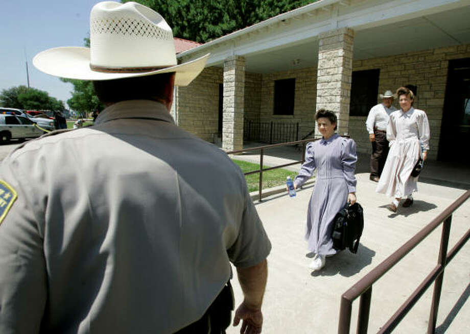 A Schleicher County deputy provides security as members of the Fundamentalist Church of Jesus Christ of Latter Day Saints leave a county building after submitting to DNA tests in Eldorado on Tuesday. A judge ordered the tests to determine family relationships in the polygamist group. Photo: Tony Gutierrez, Associated Press