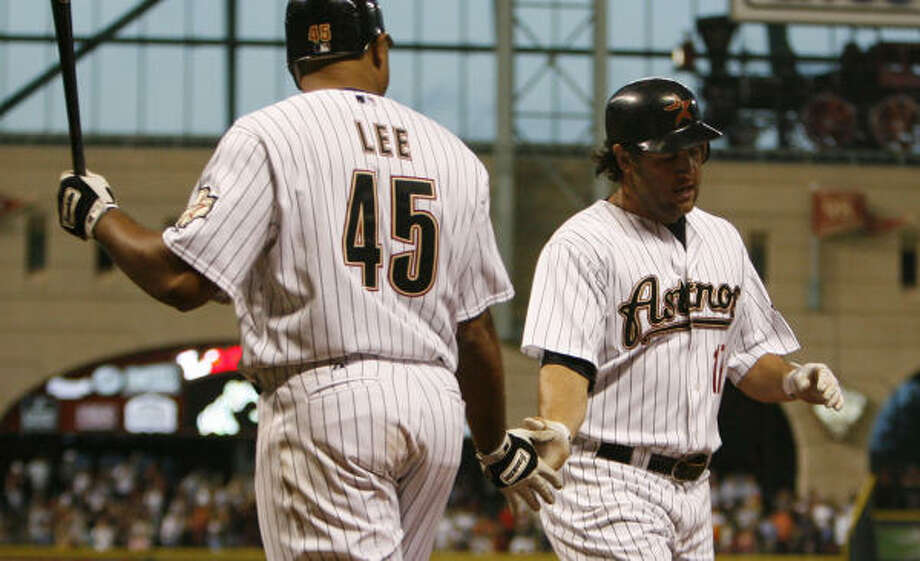 Lance Berkman (with Carlos Lee) heads for the dugout after his eighth straight hit: a homer. Photo: Karen Warren, Chronicle