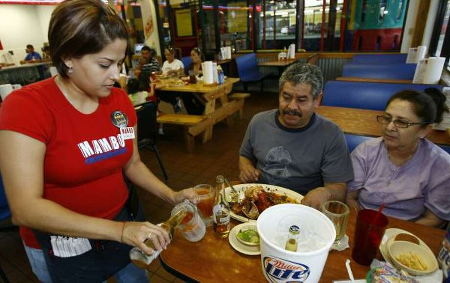 Romelia Lopez, a waitress at Mambo Seafood, pours a michelada for Hector Marquez and his wife Maria Esquivel. The Mexican restaurant chain is in a trademark battle with Anheuser-Busch Cos. because the giant beer producer contends the name is similar to its Michelob brand. Photo: NICK De La TORRE, CHRONICLE