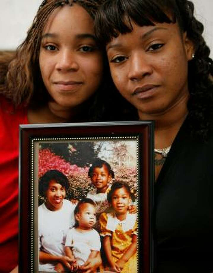 Sebrina Flowers, left, and her sister Tameka Traylor hold a picture of their family taken in 1988. Photo: STEVE CAMPBELL, CHRONICLE