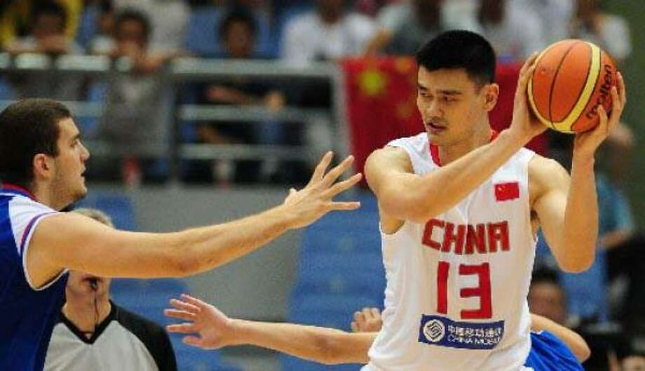 China's Yao Ming looks to pass under pressure from Serbia's Miroslav Raduljica. Photo: FREDERIC J. BROWN, AFP/Getty Images