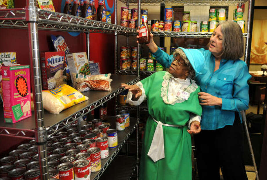 Carmen Pellettieri, right, Director of Volunteer Recruitment and Training at The Friendship Center in Conroe, helps Conroe resident Minnie Black on her visit to the center's food pantry on July 16. Photo: Jerry Baker