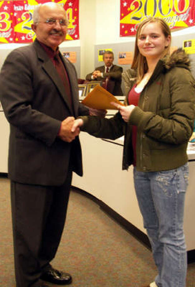 New Caney board president Gene Gregory congratulates ninth-grader Vennessa Gaas for her winning entry in the Texas Alliance for Geographic Education statewide poster contest.  More than 130,000 entries were submitted to the state competition from grades kindergarten through 12.
