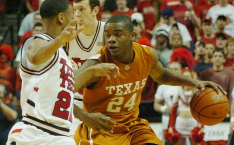 Texas guard Justin Mason tries to drive around Tech's John Roberson during the first half. Photo: JOE DON BUCKNER, AP