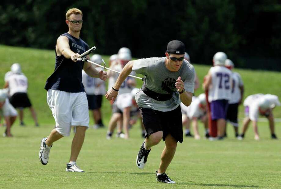 Tennessee Titans quarterbacks Rusty Smith, left, and Brett Ratliff, right, work out as the Father Ryan High School football team practices behind them on Thursday, July 21, 2011, in Nashville, Tenn. NFL owners met Thursday to discuss, and possibly vote on, a tentative deal to end the lockout that began in March. (AP Photo/Mark Humphrey) Photo: Mark Humphrey, STF / AP