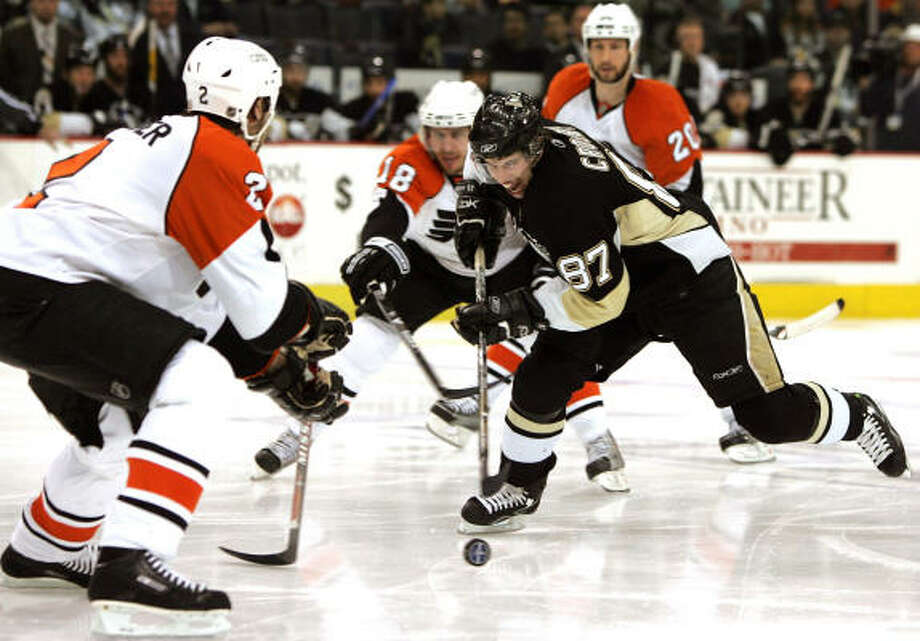 The Penguins' Sidney Crosby challenges the Flyers' Derian Hatcher, left,  during Game 2. Photo: Jim McIsaac, Getty Images