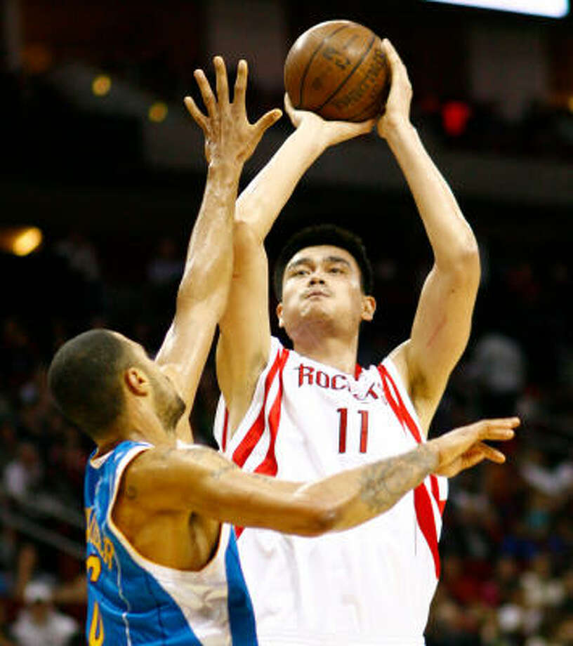 Yao Ming shoots a jumper over Hornets center Tyson Chandler in the second quarter. Photo: Nick De La Torre, CHRONICLE