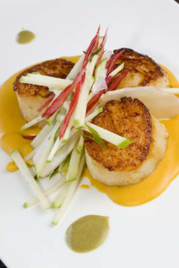 Singed scallops arrive on a sweet potato puree with accents of apple, sunchoke and a salad of Swiss chard dressed with pumpkin-seed vinaigrette. Photo: Bill Olive, For The Chronicle