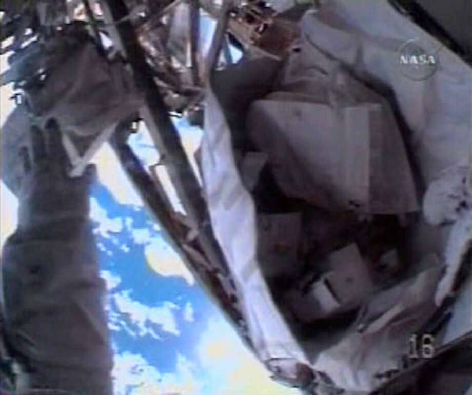 The hand of astronaut Heidemarie Stefanyshyn-Piper is seen at left, through her helmet camera, reaching for a tool kit bag that was lost from her grasp during a procedure during a space walk outside the International Space Station on Nov. 18. Photo: NASA TV, AP