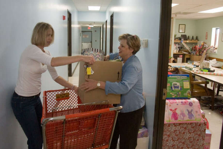 Natalie Geczik, left, and Patti Everett, a volunteer at Good Neighbor Healthcare Center, 277 W. Gray, unload gifts. Photo: R. Clayton McKee, For The Chronicle