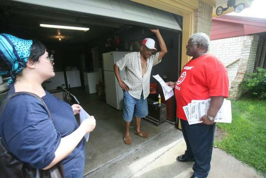 ACORN (Association of Community Organizations for Reform Now) volunteers Tóphe Nosh, left, and Lewis Jenkins, right, discuss how to avoid foreclosure with Ophell Bogany. On Wednesday, volunteers knocked on doors in parts of town that have high rates of foreclosure. Photo: STEVE CAMPBELL, CHRONICLE