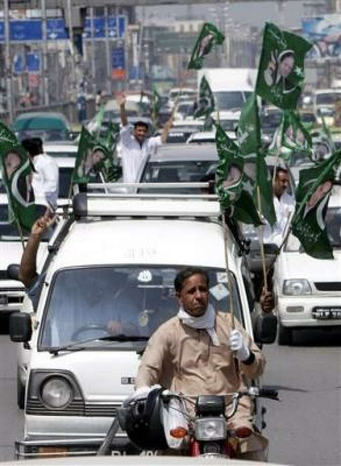 Supporters of former Pakistani Prime Minister Nawaz Sharif wave flags from vehicles during a rally in Rawalpindi today. Photo: VINCENT THIAN, Associated Press