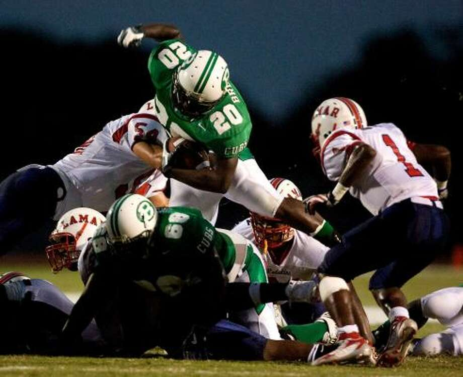 Brenham running back Ryan Roberson leaps over Lamar's Steve Erzinger (54) during the first half of the Cubs' 17-16 win on Friday. Photo: BOB LEVEY, FOR THE CHRONICLE
