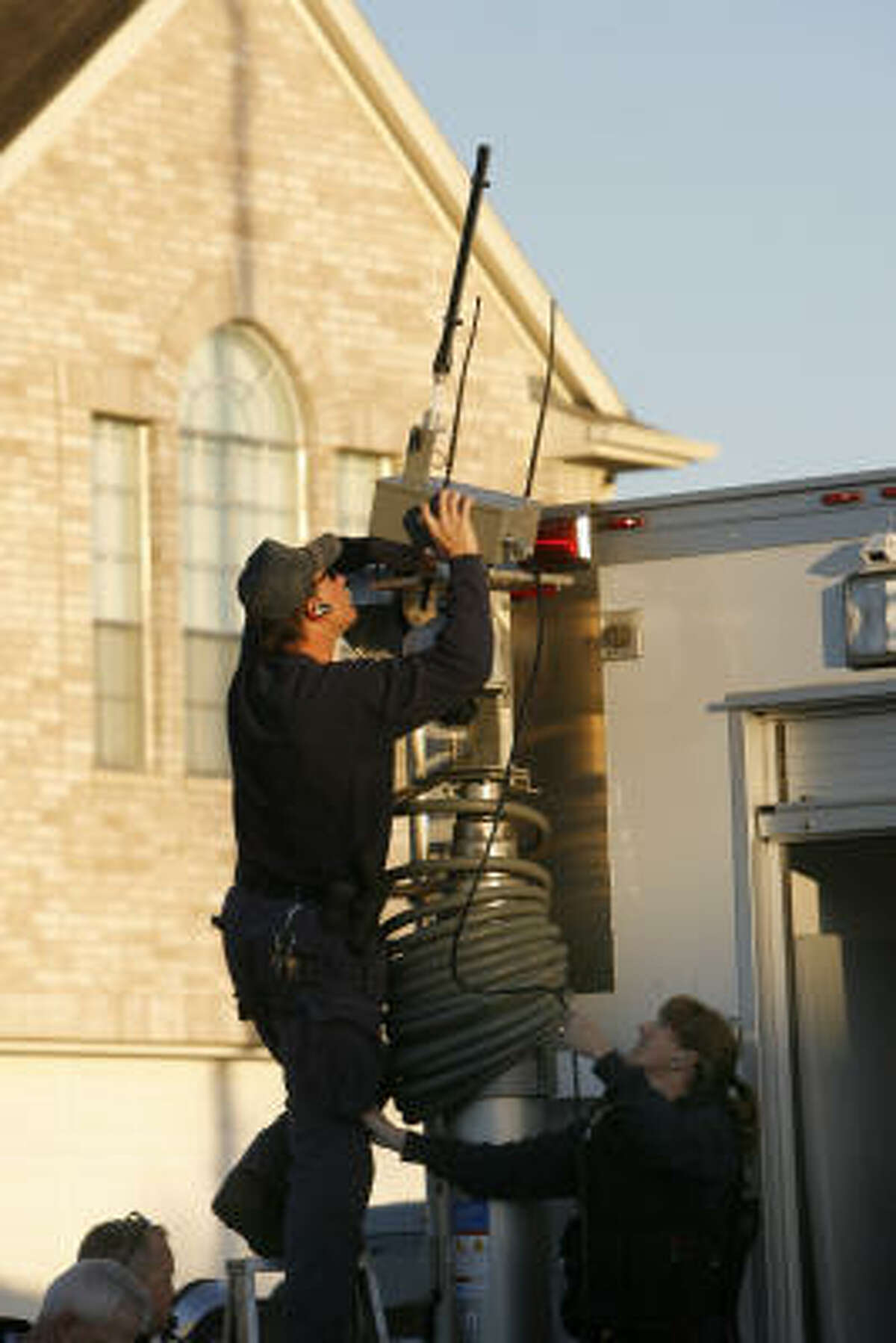 An officer installs a surveillance device on a SWAT command unit trailer during the standoff in the 21000 block of Covington Bridge in Spring.