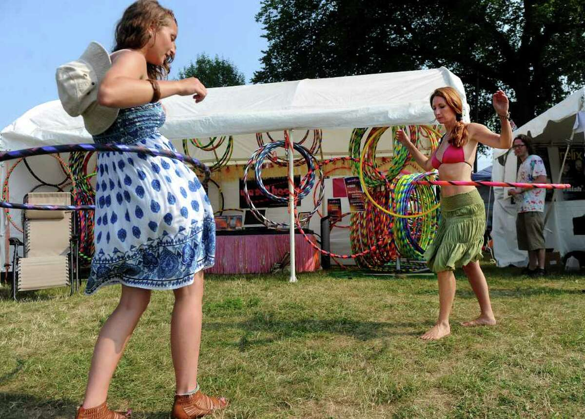 Alexandra Kirk of Newtown, Conn., left, gets a hula-hooping lesson from Mary-Beth Oliver, founder of We Sell Hoops, at the Gathering of the Vibes festival in Bridgeport on Thursday, July 21, 2011.