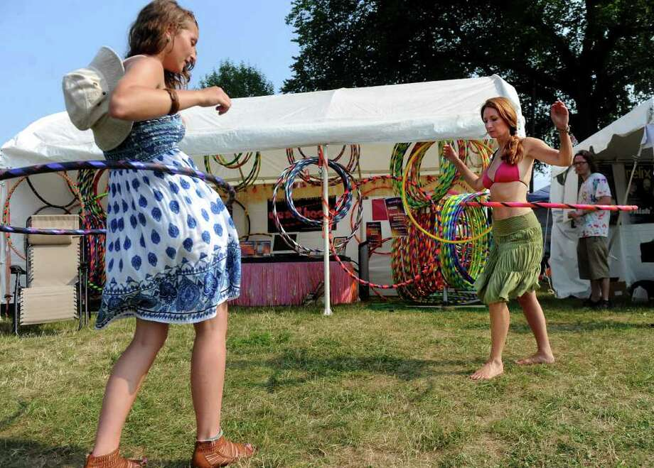 Alexandra Kirk of Newtown, Conn., left, gets a hula-hooping lesson from Mary-Beth Oliver, founder of We Sell Hoops, at the Gathering of the Vibes festival in Bridgeport on Thursday, July 21, 2011. Photo: Lindsay Niegelberg / Connecticut Post Staff