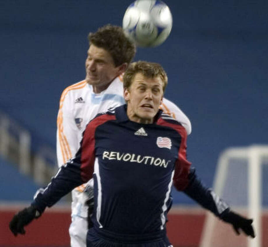 Forward Adam Cristman (front) makes contact for host New England. Photo: STEW MILNE, AP