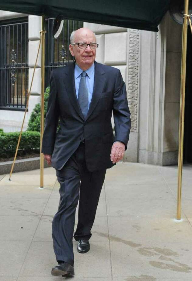 News Corporation head Rupert Murdoch exits his Fifth Avenue residence, Thursday, July 21, 2011, in New York. As the scandal runs its course in the U.K., Murdoch's News Corp. must confront at least two U.S.-based shareholder lawsuits, a possible Standard & Poor's credit downgrade, and the beginnings of a federal investigation. (AP Photo/ Louis Lanzano) Photo: Louis Lanzano, FRE / FR77522 AP