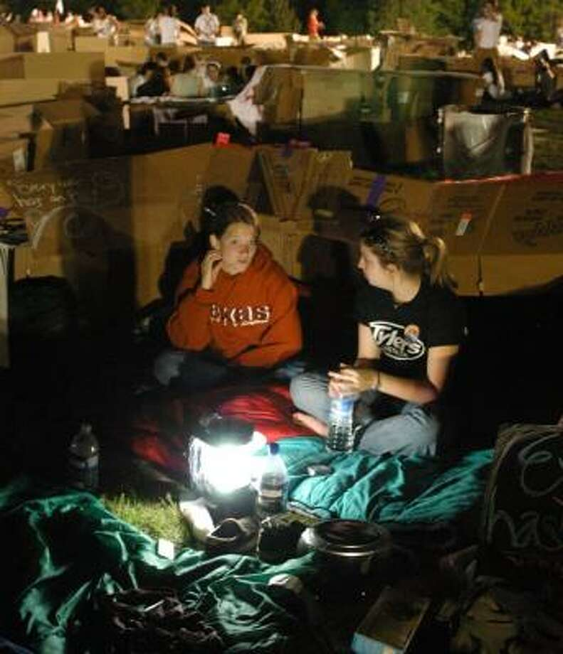 Bernadette Vingerhoets, left, and Jordan Webb prepare to wait out the night in front of the box that will serve as their sleeping quarters during the Displace Me event in Austin. About 4,000 participated. Photo: HA LAM PHOTOS, FOR THE CHRONICLE
