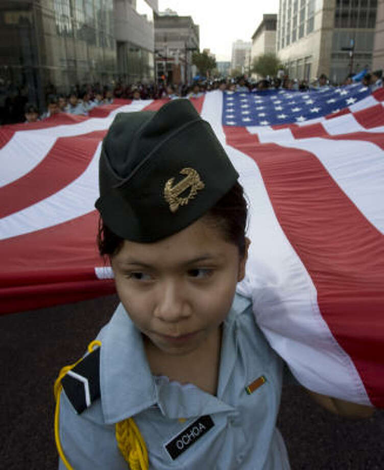 Pvt. Maria Ochoa, 14, from the Reagan High School JROTC program helps carrie an American flag down Prairie Street during the Veterans Day parade downtown Tuesday. Photo: Johnny Hanson, Chronicle