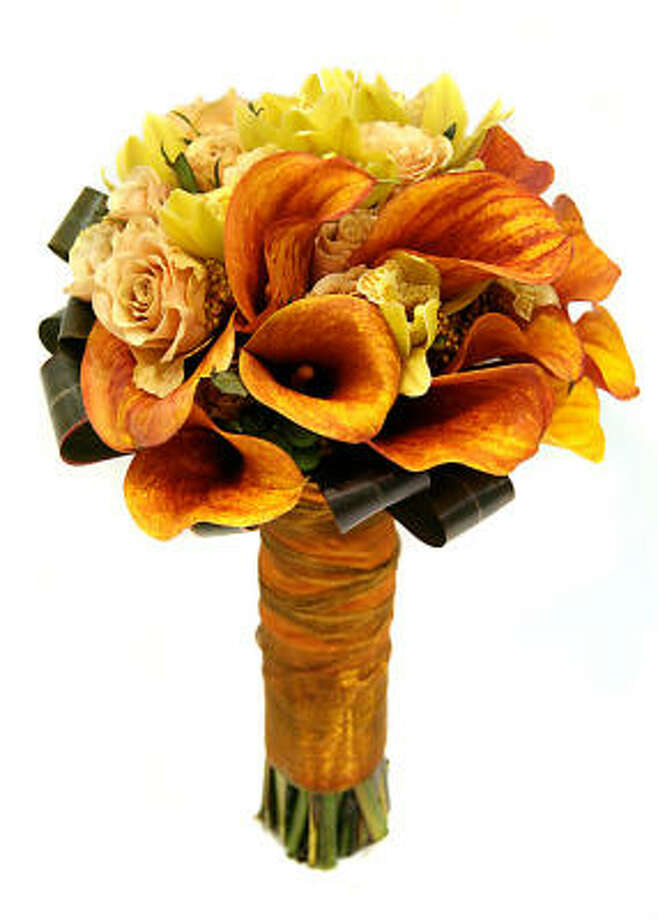 Bridal bouquets that feature roses or lilies of the valley in red, apricot or peach work well with ornate wedding gowns with long trains. Photo: Cutting Garden