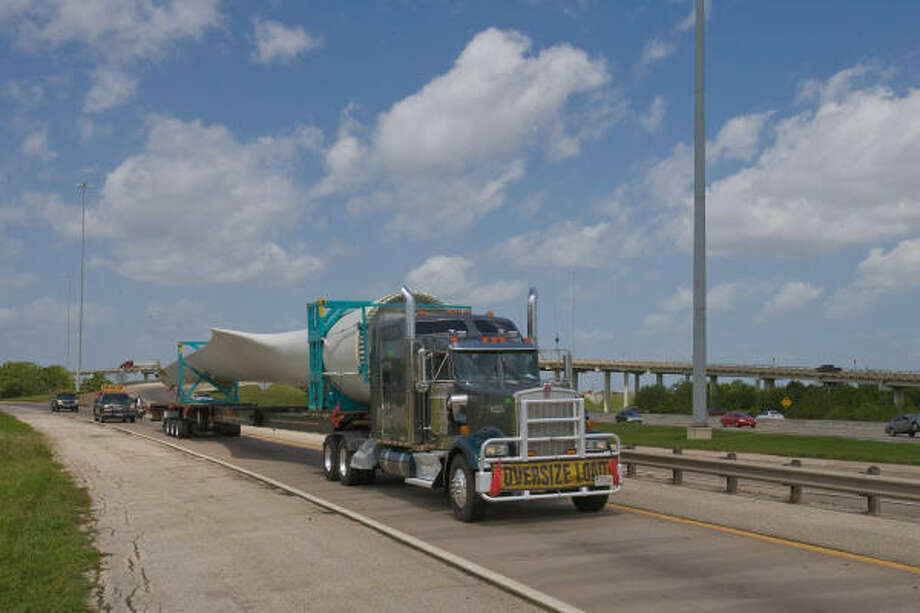 A wind turbine blade is trucked into the city, on its way to the Titan Wind Project in Miller, S.D. The truck-and-blade combo spans about 178 feet long.