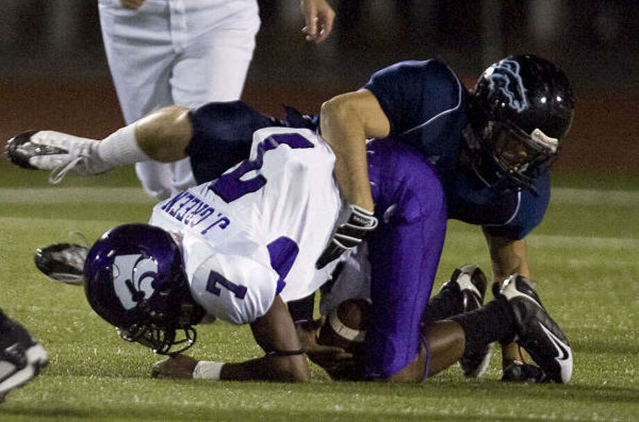 Kingwood's Dylan Ashlin makes the hit on Humble quarterback Jacobe Green. Photo: James Nielsen, Chronicle