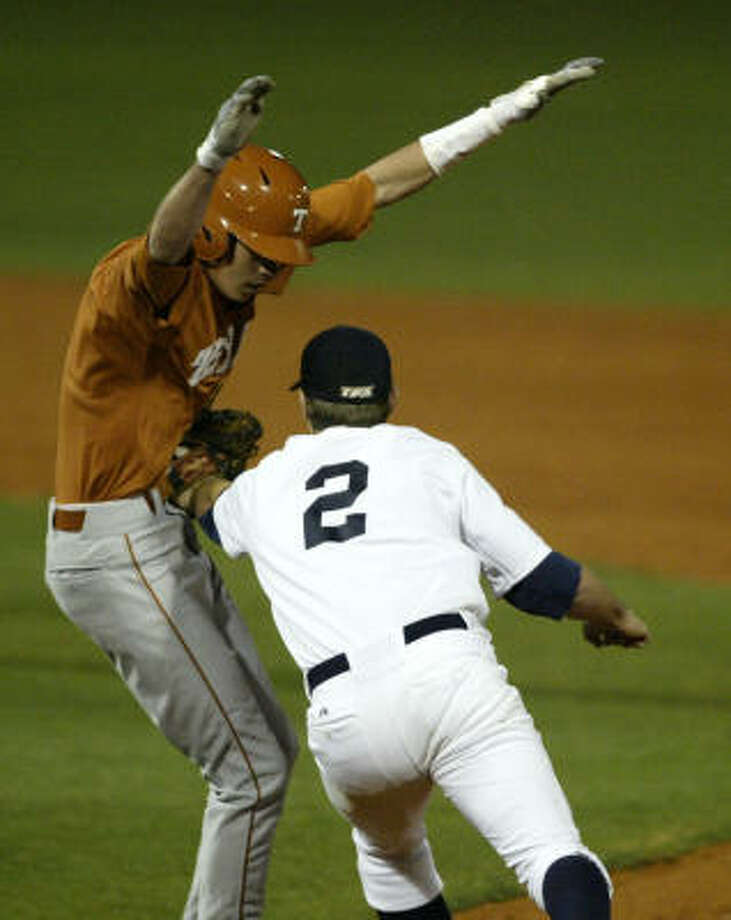 Texas outfielder Cohl Walla gets caught up in a run down by Rice first baseman Jimmy Comerota. Photo: Billy Smith II, Chronicle