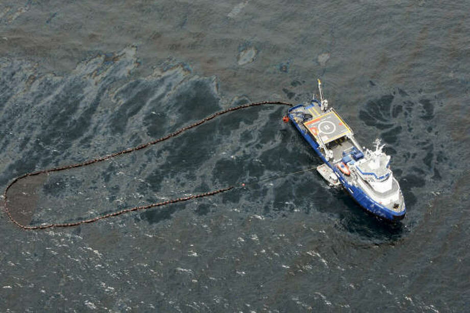 In an aerial photo taken in the Gulf of Mexico more than 50 miles southeast of Venice, La., a cleanup vessel deploys an oil boom to contain crude spilled from Tuesday's rig explosion. Photo: Gerald Herbert, Associated Press